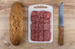 Bread, pieces of sausage on cutting board and kitchen knife Stock Images