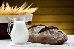Bread and pitcher of milk Stock Images
