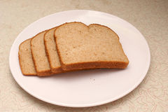 Bread on plate. Four slices of whole grain wheat bread on a plate sitting on old counter Royalty Free Stock Photos
