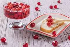Bread with plum jam on a wooden table. Homemade jam from the fresh harvest of cherry berries. Flat lay. Bread with plum jam on a wooden table. Homemade jam from royalty free stock image