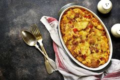 Bread pudding with bacon and cheese.Top view. Bread pudding with bacon and cheese in a baking dish over dark slate,stone or metal background.Top view Royalty Free Stock Images
