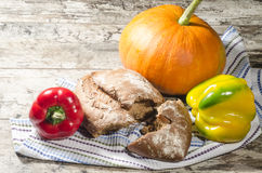 Bread, pumpkin and pepper on old wooden table Royalty Free Stock Photos