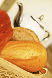 Bread ready for breakfast. Fresh bread with a tepot in the background Royalty Free Stock Photo