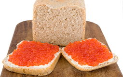 Bread and red caviar. Home-made bread and sandwiches with red caviar on an oak board isolated on white Stock Image