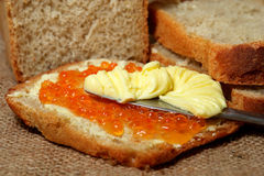 Bread with Red Caviar & Butter. Slice of bread with red caviar and whipped butter being spread on with knife, loaf and more slices of bread in background royalty free stock images