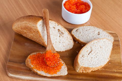 Bread with red caviar on a wooden board. Close up, horizontal Royalty Free Stock Photography