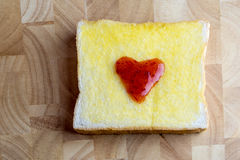 Bread and red heart shaped jam on wooden. Bread and red heart shaped jam on cutting board Royalty Free Stock Photos