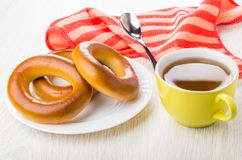 Bread rings in plate, cup of tea, teaspoon on napkin. On  wooden table Stock Photos