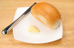 Bread roll. Knife and butter on a white plate Royalty Free Stock Images