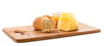 Bread roll, butter and honey on cutting board Stock Photo