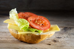 Bread roll with cheese, salad and tomatoes on  rustic wood, dark Royalty Free Stock Photo