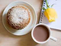 Bread roll covered with sesame seeds, a cup of cocoa. Roll covered with sesame seeds, a cup of cocoa, and yellow rose Royalty Free Stock Image