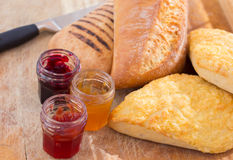 Bread-roll with jars of jam. On the cutting board breakfast preparation Royalty Free Stock Photos