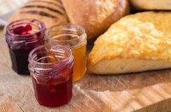 Bread-roll with jars of jam. On the cutting board breakfast preparation Royalty Free Stock Photo