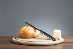 Bread roll, knive, butter, on plate. Breakfast plate with knife, bread roll and a piece of butter Stock Image