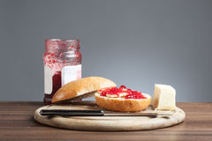 Bread roll, knive, butter, red jam on plate. Breakfast plate with knife, bread roll with red rasberry jam and a piece of butter Royalty Free Stock Photography