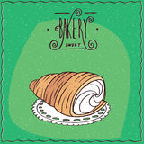 Bread roll known as torpedo dessert. Buttery, flaky viennoiserie bread roll, known as torpedo dessert, lie on a lacy napkin. Green background and lettering Stock Images