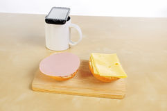 Bread roll with Mortadella and cheese with handy on cup of coffee Royalty Free Stock Photography