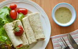 Bread roll and salad dipping sauce on table Royalty Free Stock Images