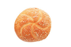 Bread roll with seeds. Freshly baked brown roll topped with sesame seeds on a white background Royalty Free Stock Image