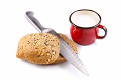 Bread roll with seeds, a kitchen knife and milk in a red mug on a white background Royalty Free Stock Photo