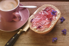 A bread roll with violet jelly Stock Photos