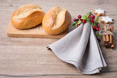 Bread rolls, linen napkin and Christmas decorations Royalty Free Stock Photo