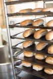 Bread rolls on trays of shelf Royalty Free Stock Image