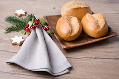 Bread rolls on wooden plate with napkin and Christmas decoration Stock Photo