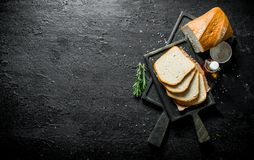 Bread with rosemary and oil on the cutting Board. On black rustic background stock photos