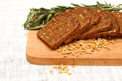 Bread, rosemary and wheat germ on a wooden board Royalty Free Stock Image