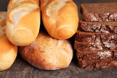 Bread. Rye bread and baguettes on wooden background royalty free stock images