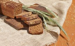 Bread rye cut with slices and ripe ears Stock Photo