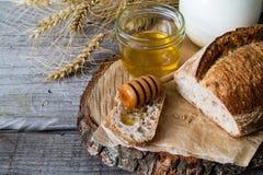 Bread, rye, wheat, honey, milk rustic wood background stock photo