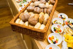 Bread and salads at the reception. Sauces in sauceboats near salads and sliced cheese on a plate for guests of a buffet table stock images