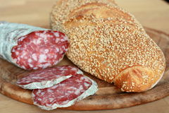 Bread and salami. Fresh crusty bread served with italian salami Stock Photography