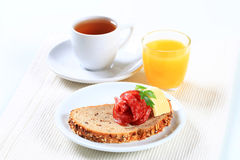 Bread with salami, tea and orange juice Royalty Free Stock Photography
