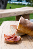 Bread with salami on wooden table Royalty Free Stock Photography