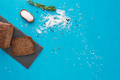 Bread and salt. Dark bread, salt and rosemary flat lay on blue background Royalty Free Stock Images