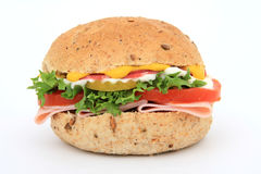 Bread sandwich in a burger bun. Brown whole grain food isolated on white, macro with copy space, lettuce, tomato and ham Royalty Free Stock Photography