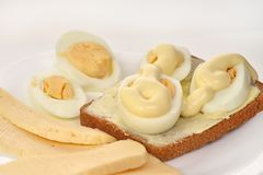 Bread sandwich with buttered eggs with mayonnaise and cheese on a white plate and white background, close-up stock photo