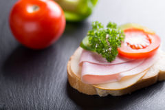 Bread or sandwich with ham and vegetables. Bread or sandwich with ham, tomato and red pepper on black background royalty free stock photos