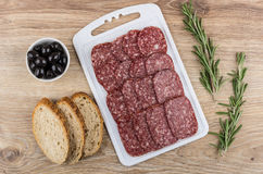 Bread, sausage on cutting board, black olives and rosemary Stock Photography