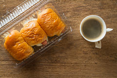 Bread with sausage in food box with paper cup of coffee on table in the morning. Royalty Free Stock Image