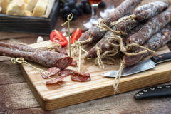 Bread, sausage, red wine, glass, cutting board and knife arranged on a wooden table for a snack in the countryside. Stock Image