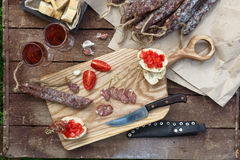 Bread, sausage, red wine, glass, cutting board and knife arranged on a wooden table for a snack in the countryside. Royalty Free Stock Image