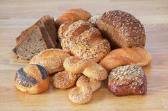 Bread with seeds. Different bread with trip sesame, sunflower, with raisins, shortening on wooden table Royalty Free Stock Photos