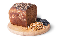 Bread with seeds on wooden board with raisins and nuts Stock Photos