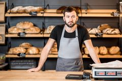 Bread seller at the bakery shop. Portrait of a handsome seller in uniform standing at the counter of the bakery shop with bread shelves on the background stock photos