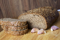 Bread with sesame grains on a wooden table. The cut long loaf Royalty Free Stock Images